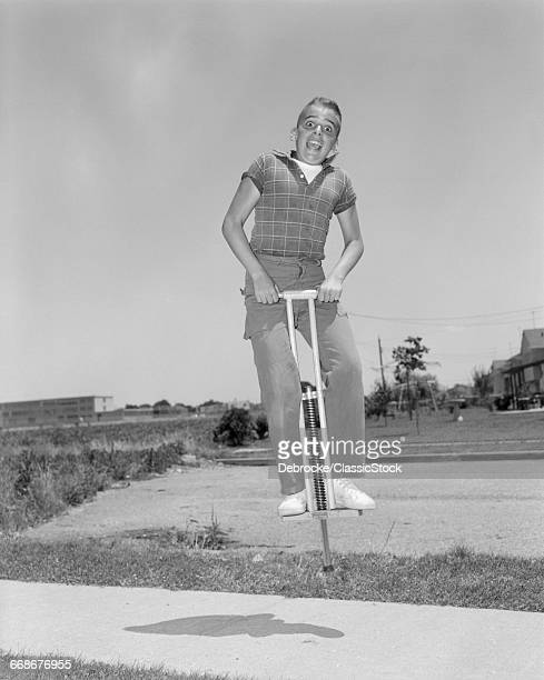 1950s BOY JUMPING ON POGO...