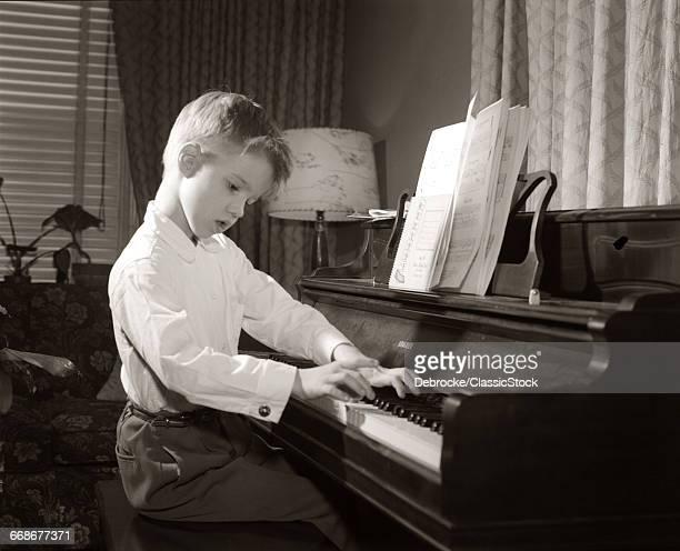1950s BOY PRACTICING PIANO...