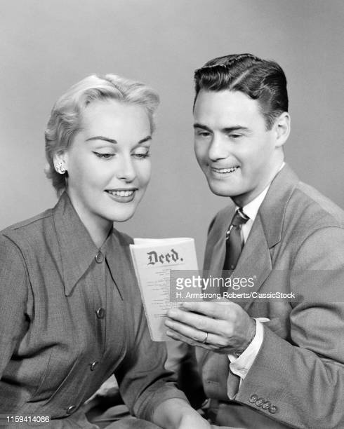 1950s BRUNETTE MAN AND BLONDE WOMAN SMILING TOGETHER LOOKING AT THE DEED TO THEIR PROPERTY