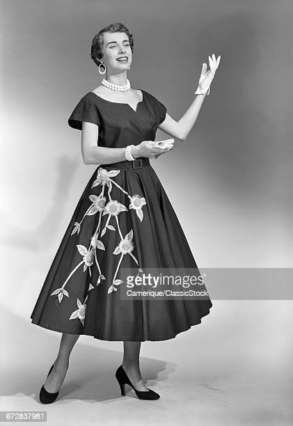 1950s BRUNETTE WOMAN WEARING BLACK DRESS WITH FLOWERS GLOVES PEARL CHOKER