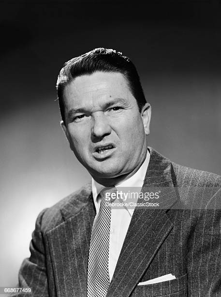 1950s BUSINESSMAN IN SUIT MAKING FUNNY SERIOUS FROWN FACIAL EXPRESSION SNEER DISGUST ANGER UNHAPPY ANGRY UNPLEASANT MEAN GROUCHY