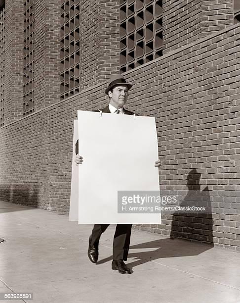 1950s BUSINESSMAN WALKING...