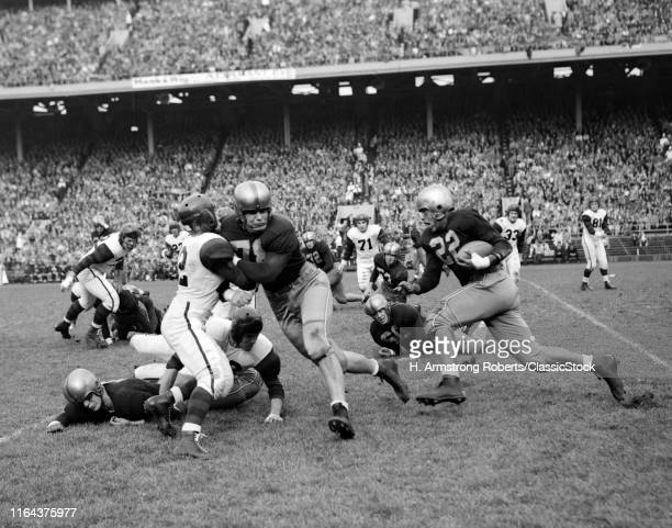 1950s College Football Game Showing Blockers Making Tackles For Running Back With Capacity Crowd In Stands In Background