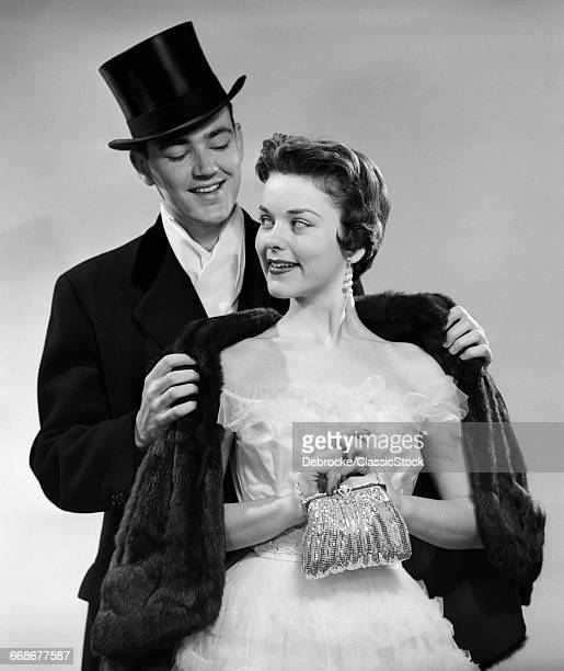 1950s COUPLE FORMAL ATTIRE MAN WEARING TOP HAT HELPING WOMAN IN EVENING CLOTHES WITH FUR STOLE