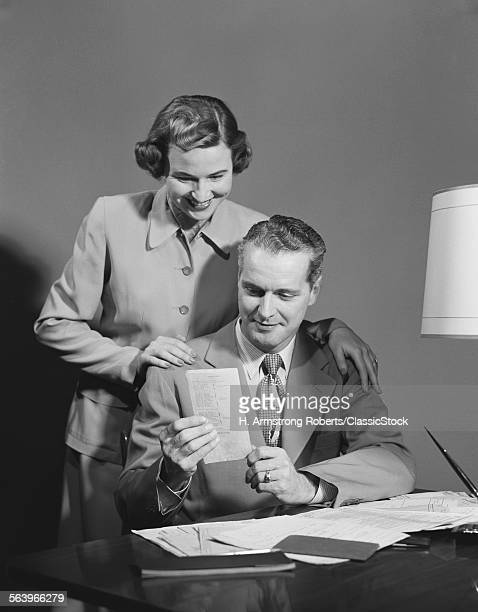 1950s COUPLE MAN SEATED AT...