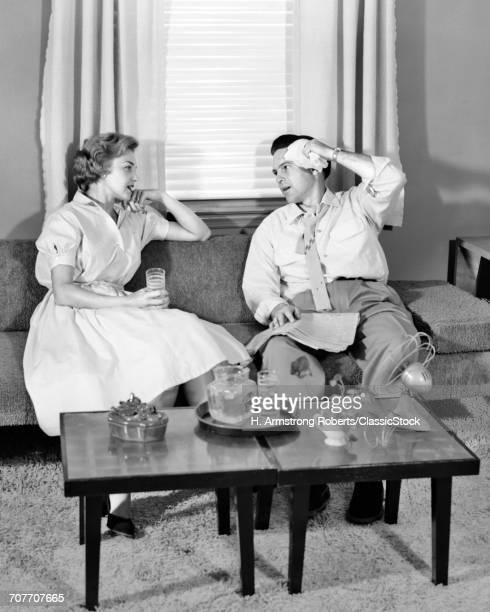 1950s COUPLE SITTING ON...