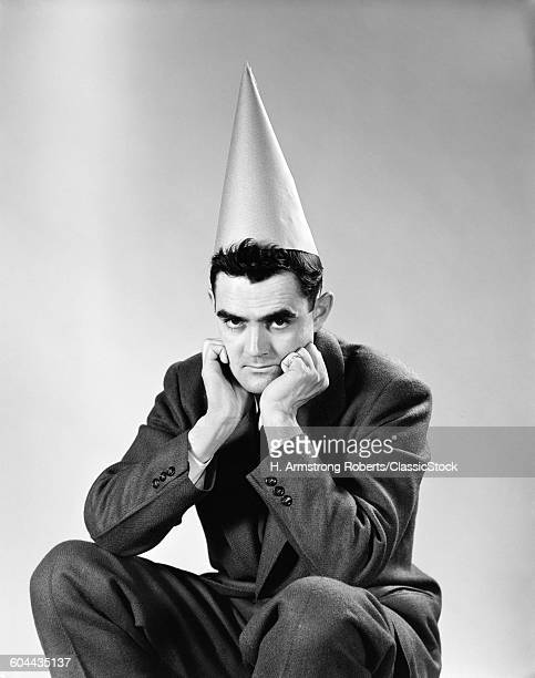 1950s DISGRUNTLED MAN WEARING DUNCE CAP LOOKING AT CAMERA