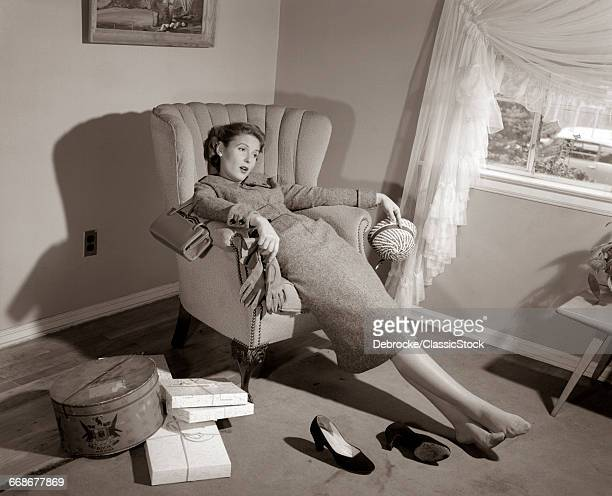 1950s EXHAUSTED FEMALE SLUMPED IN CHAIR WITH SHOES OFF AFTER SHOPPING