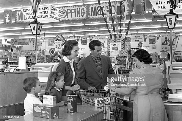 1950s FAMILY AT GROCERY...