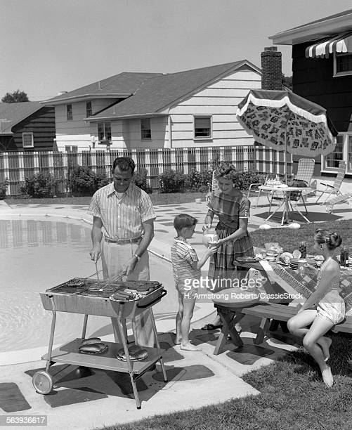 1950s FAMILY IN BACKYARD BESIDE POOL HAVING COOKOUT OF HOT DOGS & HAMBURGERS