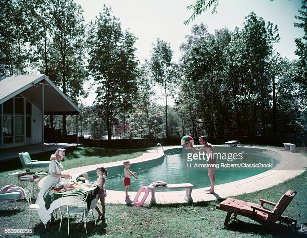 1950s FAMILY MAN WOMAN SON DAUGHTER FOUR BACKYARD KIDNEY SWIMMING POOL PICNIC FOOD BEACH BALL HOUSE TREES SUMMER