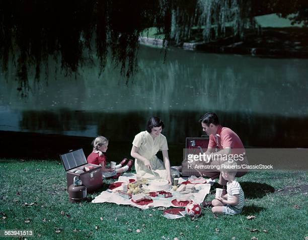 1950s FAMILY PICNIC BY POND LAKE MOM DAD BOY GIRL WILLOW TREE TABLECLOTH SPREAD COOLER THERMOS BASKET FOOD SUMMER MEAL