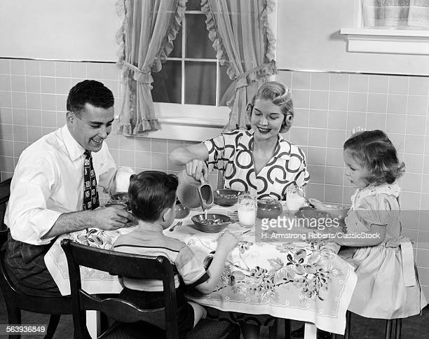 1950s FAMILY SITTING AT...