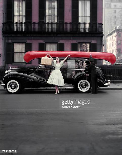 Fashion model Barbara Mullen poses arms wide and mouth open in front of a model dressed as a chauffer tying a red canoe onto a black Rolls-Royce in...