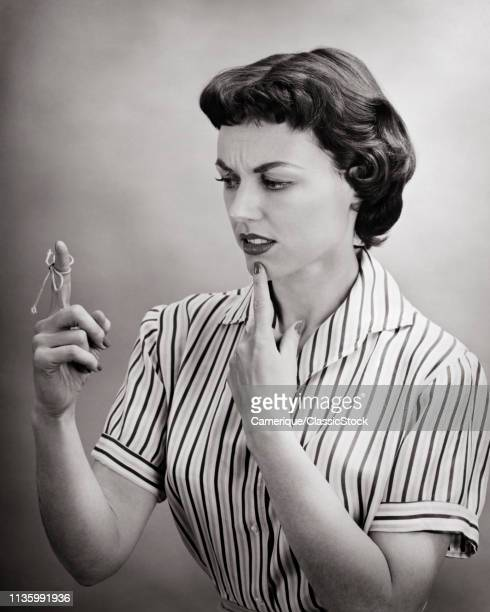 1950s FORGETFUL CONFUSED WOMAN HOUSEWIFE TRYING TO REMEMBER SOMETHING LOOKING AT REMINDER STRING TIED ON FINGER