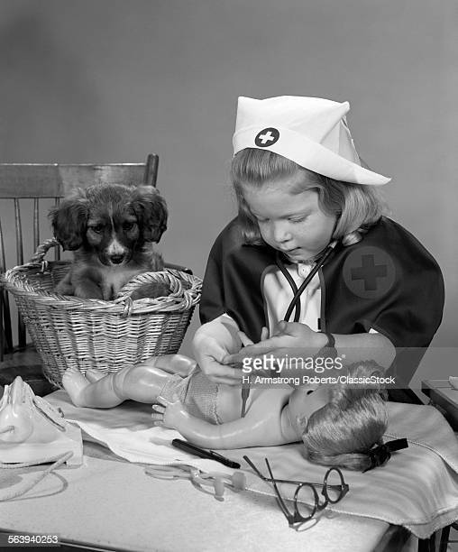 1950s GIRL WEARING NURSE'S UNIFORM PUTTING BANDAGES ON A DOLL WHILE A PUPPY DOG IN A BASKET BEHIND HER WATCHES