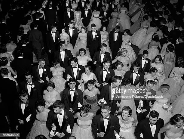 1950s GRAND MARCH AT HIGH SCHOOL PROM TEEN COUPLES WEARING FORMAL DRESS