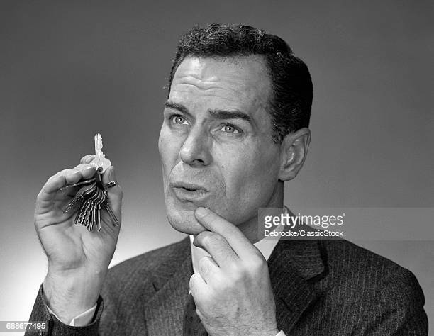 1950s HEAD SHOT OF MAN HOLDING PAIR OF KEYS POINTING TO CHIN INDOOR MEMORY REMEMBER FACE EXPRESSION THINKING