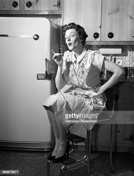 1950s HOUSEWIFE SITTING ON STOOL IN KITCHEN POINTING FINGER LOOKING AT CAMERA