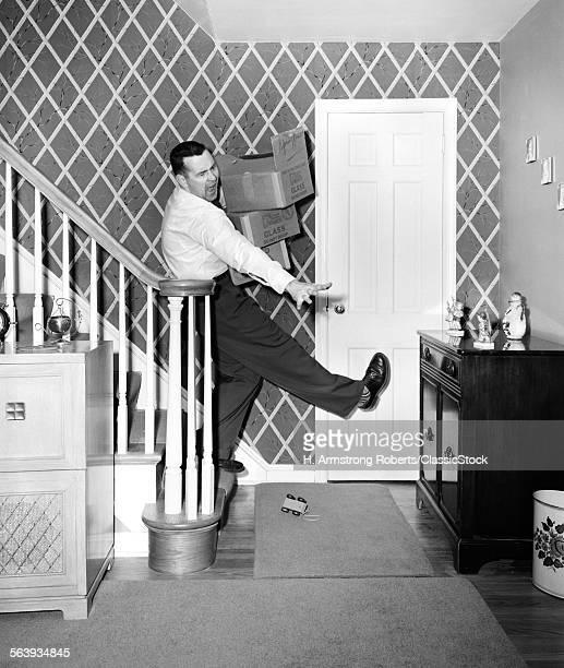 1950s MAN CARRYING STORAGE...