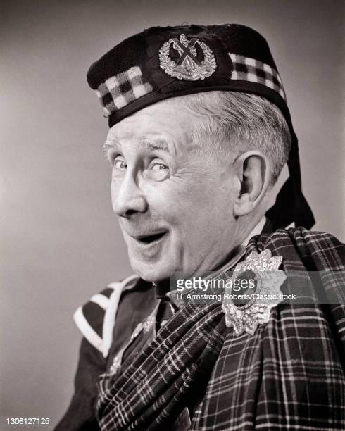 1950s Man Wearing scottish Military Jacket & sash Cairngorm Brooch & Glengarry With Cameron Highlanders Badge Looking At Camera.