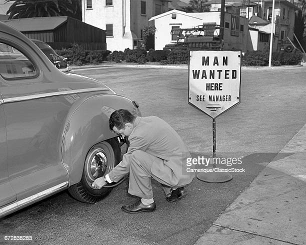 1950s MAN WEARING SUIT PUTTING AIR IN AUTOMOBILE TIRE NEXT TO HELP WANTED SIGN