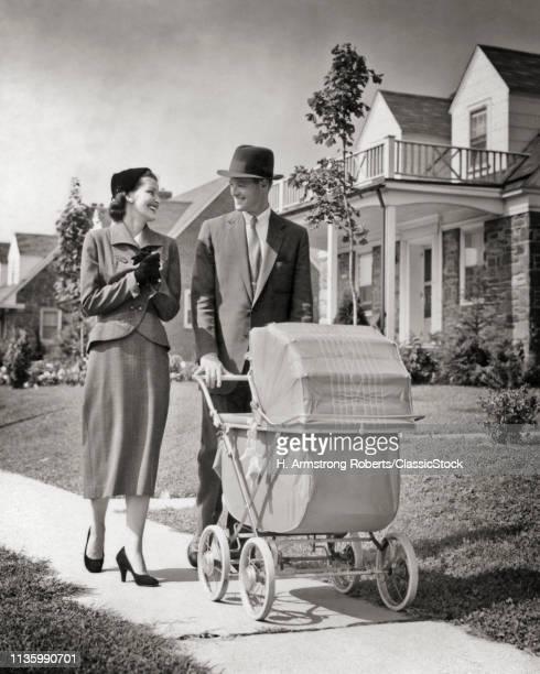1950s MAN WOMAN PUSHING...