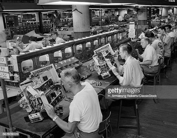 1950s MEN IN ELECTRONICS FACTORY WORKING ON TELEVISION ASSEMBLY LINE INDOOR