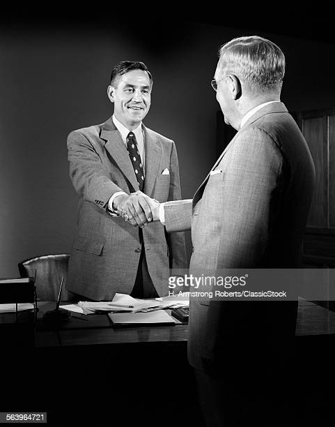 1950s MEN SHAKING HANDS SUITS DESK BUSINESS PAPER WORK