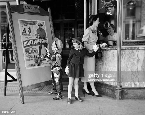 1950s MOTHER 2 CHILDREN BUYING TICKETS TO MOVIE MATINEE BOY WEARING COWBOY COSTUME