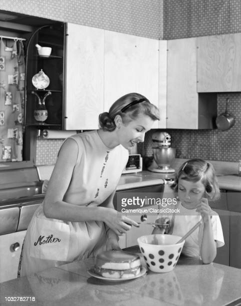 1950s MOTHER AND DAUGHTER IN KITCHEN FROSTING DOUBLE LAYER CAKE WORD MOTHER ON APRON