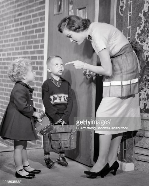 1950s Mother Shaking Her Finger Talking To Boy And Girl At Front Door Before Kids Leave For School Giving Safety Instructions