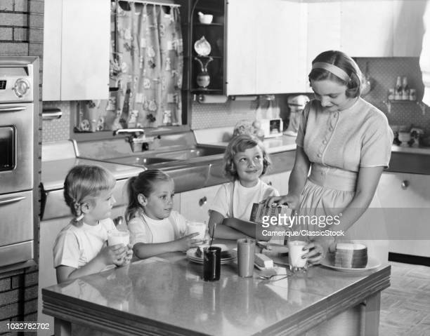 1950s MOTHER THREE DAUGHTERS STANDING AROUND KITCHEN TABLE MAKING LUNCH PEANUT BUTTER JELLY SANDWICHES MOTHER POURING GLASS MILK
