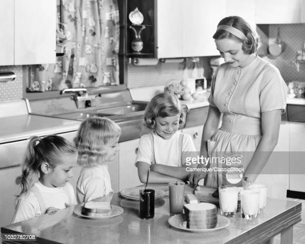 1950s MOTHER & THREE DAUGHTERS STANDING AT KITCHEN TABLE MAKING LUNCH PEANUT BUTTER & JELLY SANDWICHES & GLASSES OF MILK