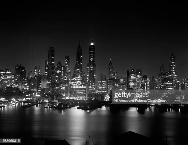 1950s NIGHT SKYLINE EMPIRE STATE BUILDING ABOVE HUDSON RIVER MIDTOWN MANHATTAN NEW YORK CITY USA