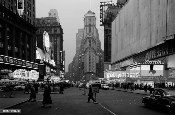 1950s NIGHT TIMES SQUARE LOOKING SOUTH FROM DUFFY SQUARE TO NY TIMES BUILDING MOVIE MARQUEES NEW YORK CITY NY USA