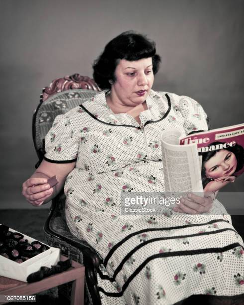 1950s OBESE OVERWEIGHT WOMAN SITTING EATING BOX OF CHOCOLATE CANDY READING MOVIE FAN MAGAZINE