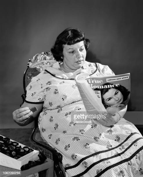 1950s OVERWEIGHT WOMAN EATING CANDY AND READING TRUE ROMANCE MAGAZINE