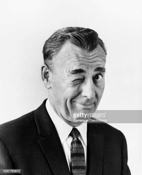 1950s PORTRAIT BUSINESS MAN LOOKING AT CAMERA WINKING HIS RIGHT EYE