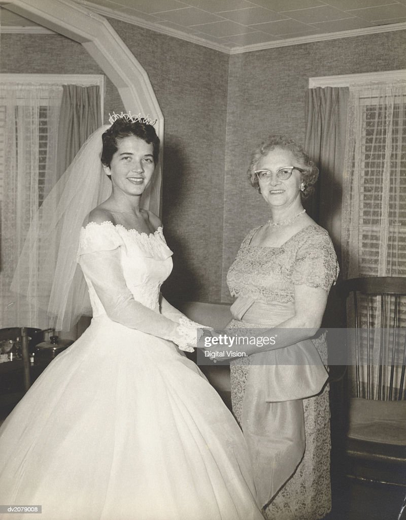 1950s Portrait of a Woman in a Wedding Dress Holding Hands With Her Mother : Stock Photo