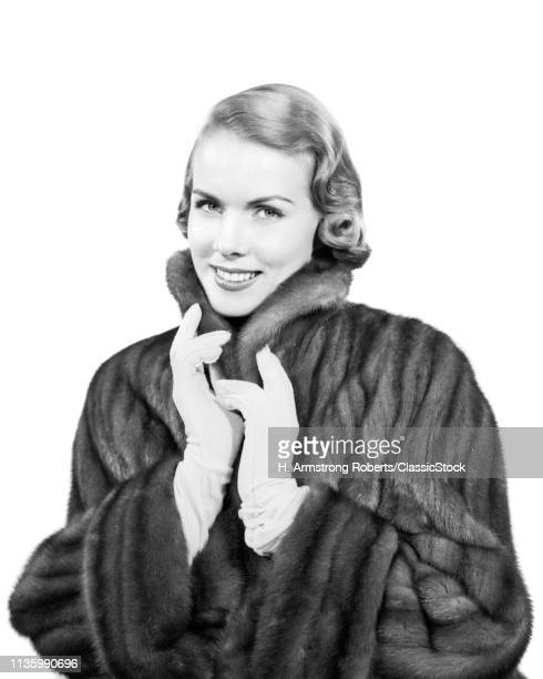 1950s PORTRAIT SMILING WOMAN WEARING FUR COAT GLOVES LOOKING AT CAMERA