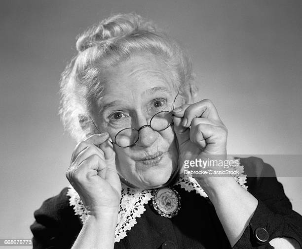 1950s PORTRAIT OF SMILING OLD LADY HOLDING HER ANTIQUE WIRE FRAME GLASSES