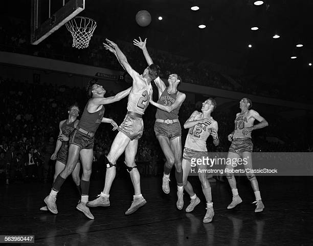 1950s PROFESSIONAL NBA BASKETBALL GAME BALTIMORE BULLETS AND PHILADELPHIA WARRIORS BALL IS IN AIR PLAYERS JUMPING FOR REBOUND