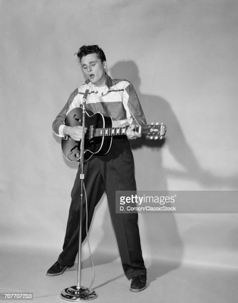 1950s ROCKABILLY SINGER IN FRONT OF MICROPHONE STRUMMING HOLLOWBODY GUITAR
