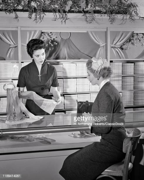 1950s SALESWOMAN HELPING A WOMAN SEATED AT THE HOSIERY COUNTER OF DEPARTMENT STORE