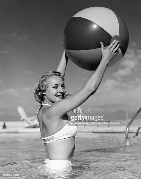 1950s SIDE VIEW OF BLONDE IN WHITE BIKINI STANDING IN POOL IN WAISTHIGH WATER HOLDING BEACH BALL IN AIR