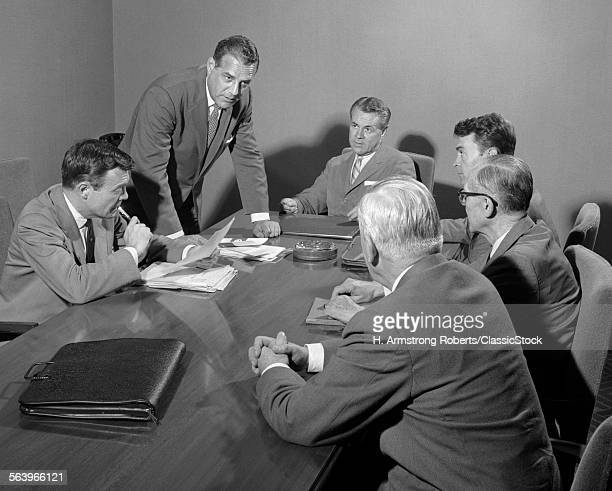 1950s SIX BUSINESSMEN EXECUTIVES AROUND A CONFERENCE TABLE TALKING
