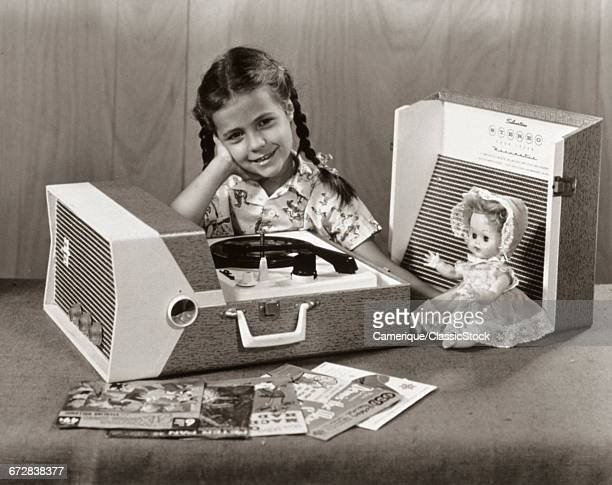 1950s SMILING GIRL LISTENING TO PORTABLE RECORD PLAYER LOOKING AT CAMERA
