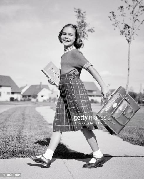 1950s Smiling Preteen Young Lady Looking At Camera Walking Briskly To School Wearing Plaid Skirt And Sweater Carrying Book Bag