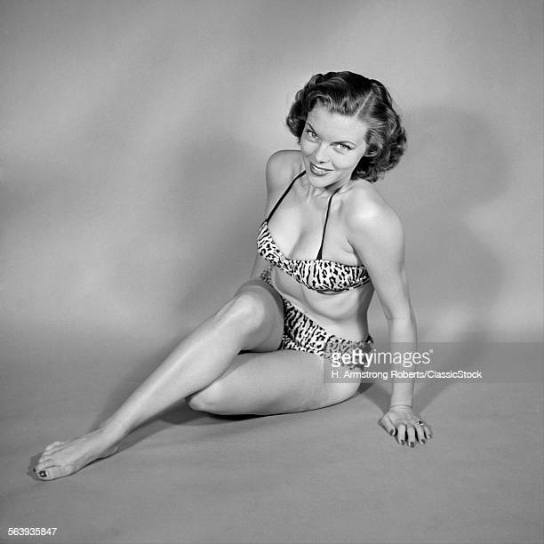 1950s SMILING SEATED WOMAN BATHING BEAUTY PINUP IN LEOPARD SKIN SPOTTED BIKINI LOOKING AT CAMERA